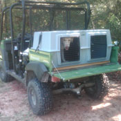 A Hunting Dog in an Easy Loader Kennel on an Offroad Vehicle