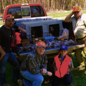 Four hunters pose with their dogs in an Easy Loader Kennel, showing off their successful hunt.
